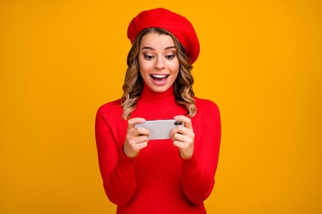Retrato de close-up dela ela agradável atraente alegre alegre alegre menina de cabelos ondulados segurando na célula de mãos jogando jogo estratégico se divertindo isolado em fundo de cor amarela vibrante brilho vívido brilhante