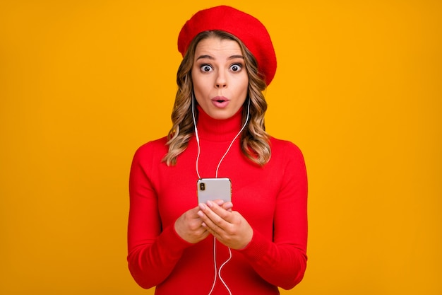 Retrato de close-up dela, ela agradável atraente espantada alegre garota de cabelos ondulados segurando nas mãos celular ouvindo podcast música beicinho lábios isolados em fundo de cor amarela vibrante brilho vívido brilhante