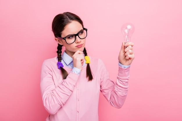 Retrato de close-up dela, ela agradável atraente mente suspeita criativa de cabelos castanhos adolescente segurando a lâmpada na mão criando solução decisão isolado fundo de cor rosa pastel