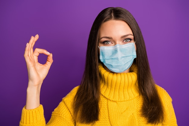 Retrato de close-up dela ela atraente garota de cabelos castanhos usando máscara de gaze parar contaminação doença cobre síndrome de influenza mostrando ok-sinal de vida saudável isolada no fundo de cor violeta
