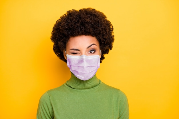 Retrato de close-up dela ela atraente garota de cabelos ondulados usando máscara de segurança ar co2 poluição ambiente mers cov pandemia piscando isolado vívido brilhante vibrante brilho amarelo cor de fundo
