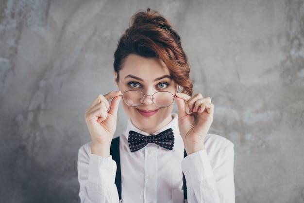 Retrato de close-up dela, ela bonita atraente adorável fofa conteúdo alegre tímida garota de cabelos ondulados funcionário profissional tocando especificações isoladas no fundo cinza da parede industrial de concreto