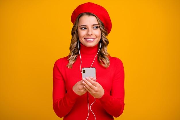 Retrato de close-up dela ela bonita atraente muito alegre garota de cabelos ondulados segurando nas mãos celular ouvindo rock soul pop isolado em fundo de cor amarela vibrante brilho vívido brilhante