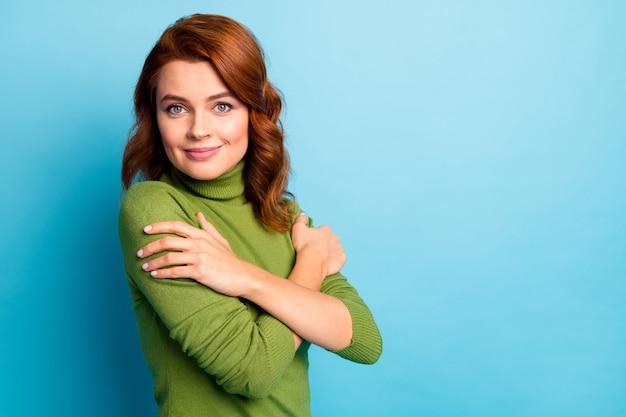 Retrato de close-up dela, ela é agradável, atraente, alegre, sonhadora, suave, terna, menina, de cabelos ondulados, abraçando-se com roupas macias, isoladas sobre uma parede de cor azul turquesa azul turquesa brilhante brilho vívido brilhante