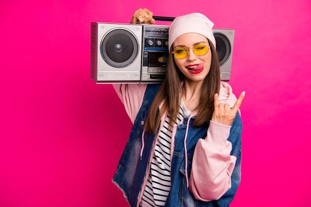 Retrato de close-up dela, ela é legal, atraente, alegre, alegre, garota carregando uma caixa de som mostrando o sinal de chifre fazendo uma careta, se divertindo, isolado em um brilho vívido brilhante rosa vibrante