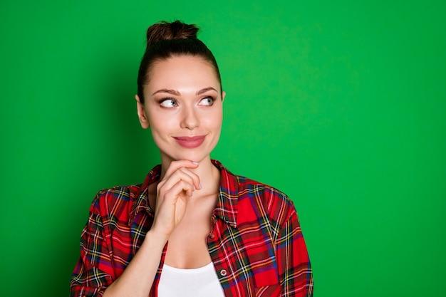 Retrato de close-up dela, ela é legal, atraente, criativa, inteligente, garota de cabelos castanhos, vestindo uma camisa xadrez, pensando, tocando chique, isolado sobre um fundo de cor verde vibrante de brilho vívido brilhante