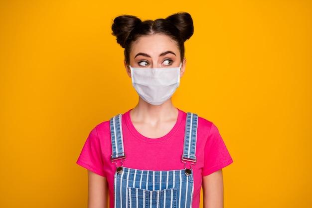 Retrato de close-up dela, ela é legal, atraente, muito curiosa, de cabelos castanhos, usando máscara de segurança, olhando de lado, medidas preventivas de doenças respiratórias isoladas fundo de cor amarela vibrante