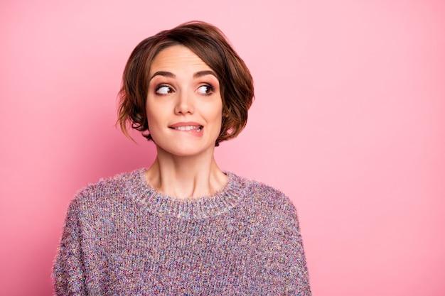 Retrato de close-up dela ela legal atraente adorável adorável muito fofo charmoso feminino engraçado menina de cabelos castanhos insegura mordendo o lábio olhando de lado isolada sobre parede rosa