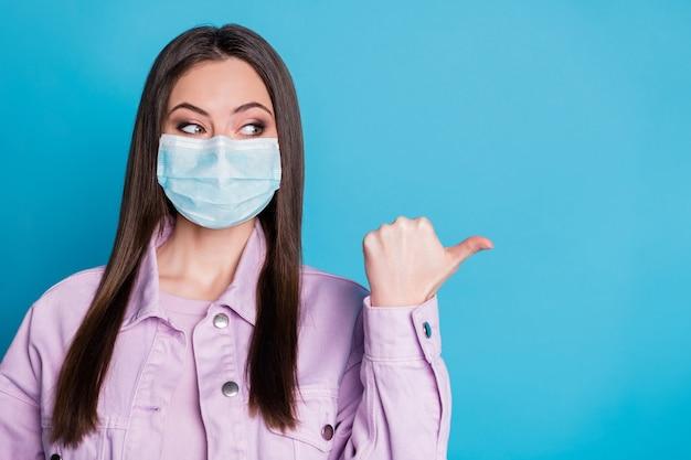 Retrato de close-up dela, garota atraente e confiante usando máscara de segurança de gaze mostrando cópia espaço em branco vazio parar pandemia medicina isolado brilhante brilho vívido fundo de cor azul vibrante