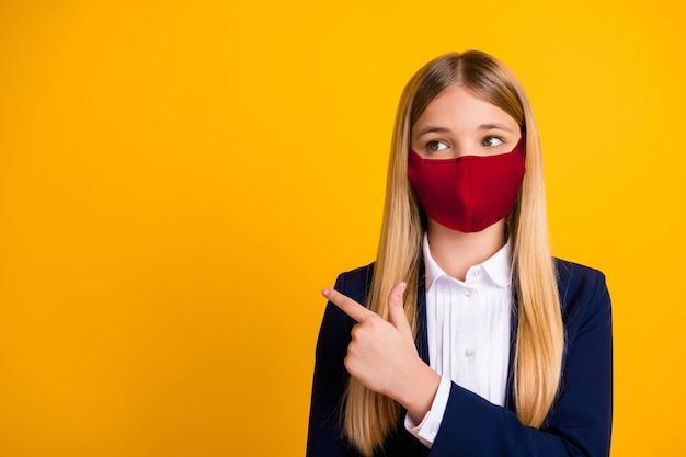 Retrato de close-up dela, linda, adorável, de cabelos compridos, estudante saudável, usando máscara reutilizável de tecido vermelho de segurança, demonstrando o espaço da cópia isolado brilhante brilho vívido fundo de cor amarela vibrante