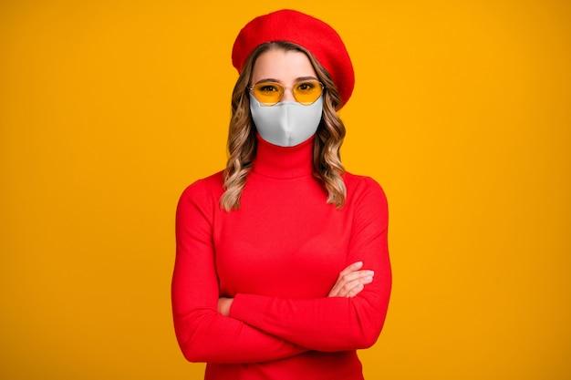 Retrato de close-up dela, linda, charmosa, muito alegre, de cabelos ondulados, braços cruzados e máscara médica isolada em um fundo de cor amarelo brilhante.