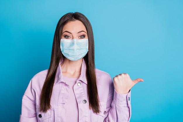 Retrato de close-up dela, menina bonita, atraente, confiante e saudável, usando máscara de segurança de gaze, mostrando cópia espaço mers cov prevenção de pneumonia isolado brilhante brilho vívido vibrante fundo de cor azul