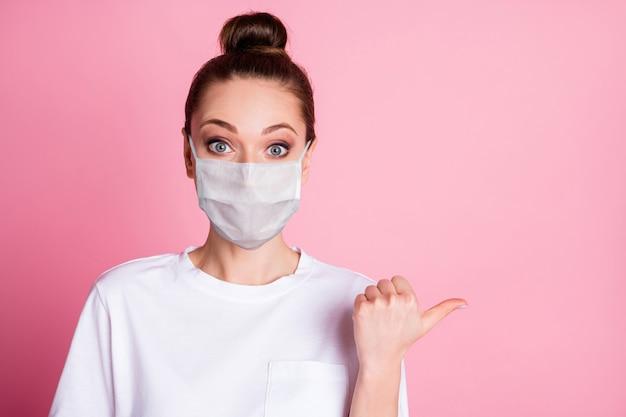 Retrato de close-up dela, menina bonita, atraente, espantada, usando máscara de segurança, mostrando cópia espaço mers cov prevenção contra influenza vacina novidade medicare isolado fundo de cor rosa pastel