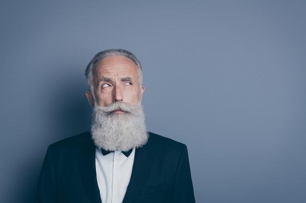 Retrato de close-up dele ele agradável atraente duvidoso suspeito homem de cabelos grisalhos vestindo smoking smoking adivinhando pista pensando criando estratégia isolada sobre fundo cinza pastel