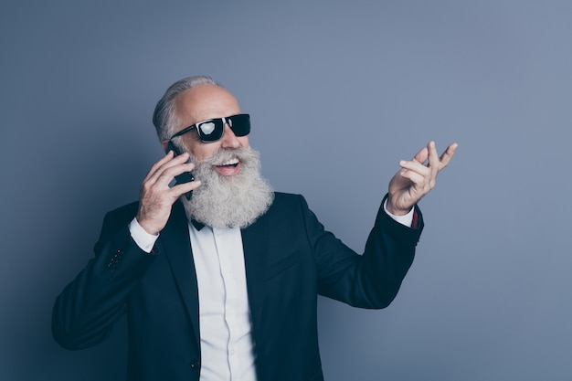 Retrato de close-up dele ele bom atraente chique elegante na moda alegre alegre homem de cabelos grisalhos usando óculos de smoking ligando para casa em roaming isolado sobre fundo cinza escuro