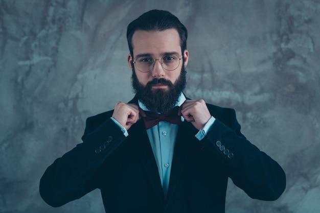 Retrato de close-up dele, ele bonito atraente imponente representante sério barbudo vestindo smoking de veludo fixando arco isolado sobre parede industrial de concreto cinza