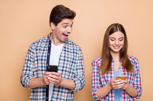 Retrato de close-up dele ele ela ela agradável atraente adorável alegre alegre casal vestindo camisa xadrez criando um novo post smm como seguir assinar isolado sobre fundo bege
