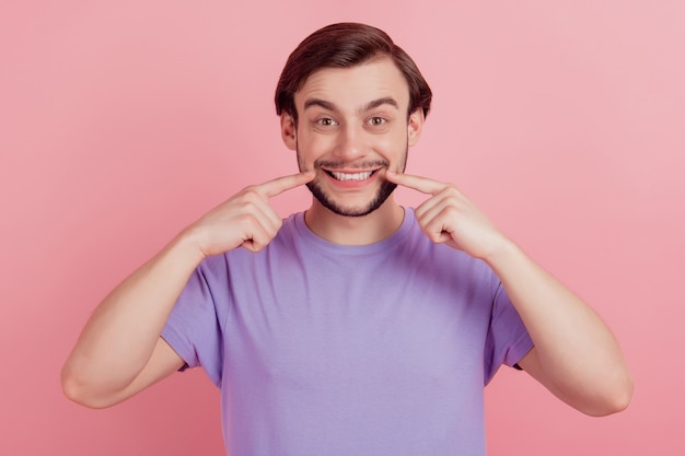 Retrato de close-up do cara positivo indica efeito de sorriso dentuço dos dedos isolado no fundo de cor rosa