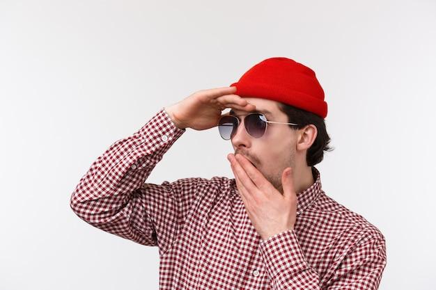 Retrato de close-up do homem caucasiano chocado e sem palavras de gorro vermelho e óculos de sol, ofegante boca de descrença e tremeu, olhar para longe, encontrou algo chocante, ficar parede branca