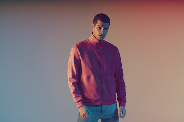 Retrato de close-up do modelo masculino atraente. luz do flash colorida