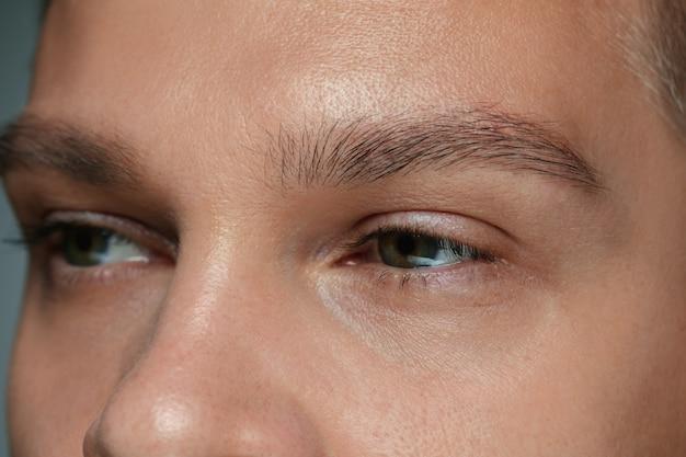 Retrato de close-up do rosto de um jovem isolado na parede cinza do estúdio