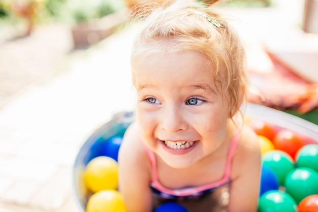Retrato de close-up garota liitle. garota está em uma piscina com balões multicoloridos. horário de verão.