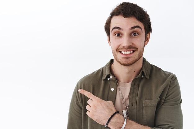 Retrato de close-up homem sorridente feliz com barba apontando para a esquerda no anúncio, sugira clique no banner