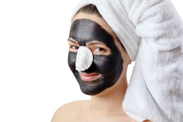 Retrato de close-up mulher bonita engraçada com máscara facial preta em fundo branco, garota com uma toalha branca na cabeça, sorriso satisfeito e feliz, mimos, situação cômica