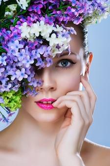 Retrato de close-up preto e branco pintado de menina com maquiagem elegante e flores ao redor de seu rosto