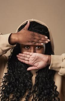 Retrato de close-up vertical de jovem afro-americana, escondendo o rosto enquanto posava em um fundo bege neutro em estúdio, copie o espaço