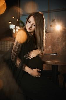 Retrato de closeup elegante de uma jovem grávida com maquiagem brilhante em um vestido preto da moda em ...