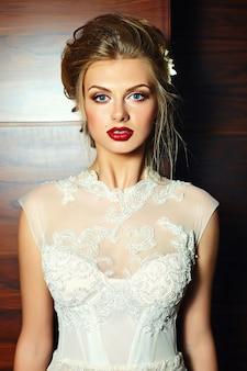 Retrato de closeup glamour da noiva loira linda com maquiagem brilhante e lábios vermelhos