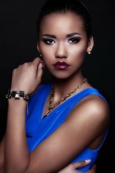 Retrato de closeup glamour do modelo sexy preto elegante mulher sexy vestido azul com acessórios com maquiagem brilhante com perfeita pele limpa