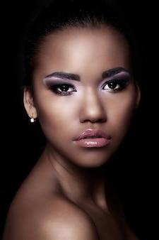 Retrato de closeup glamour do modelo sexy preto jovem bonita com maquiagem brilhante com pele limpa perfeita