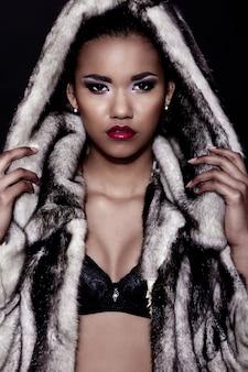 Retrato de closeup glamour do modelo sexy preto jovem bonita com maquiagem brilhante com perfeita limpeza com lábios vermelhos com casaco de pele