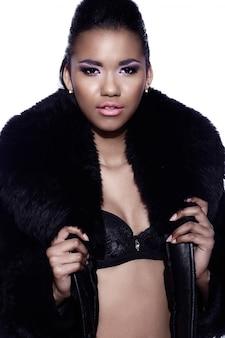 Retrato de closeup glamour do modelo sexy preto jovem bonita com maquiagem brilhante com perfeito limpo com casaco de pele
