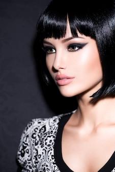 Retrato de clouseup de mulher bonita com maquiagem glamour brilhante e cabelo preto curto e liso posando