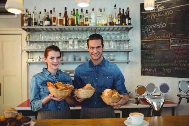Retrato de colegas de trabalho felizes com pães no café
