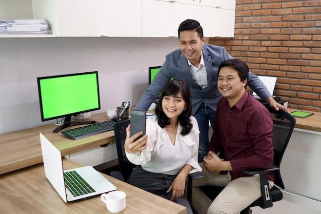 Retrato de colegas de trabalho felizes. quem está fazendo selfie juntos em sua mesa de escritório moderna