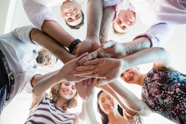 Retrato de colegas de trabalho sorridentes com as mãos empilhadas