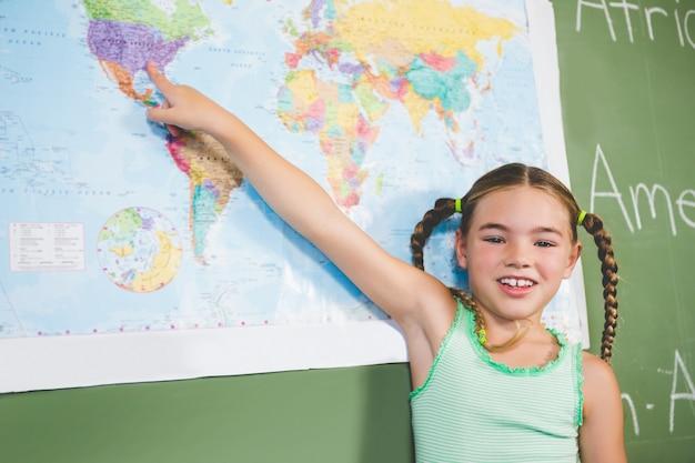 Retrato de colegial, apontando para o mapa na sala de aula
