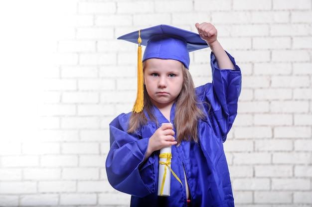 Retrato de colegial bonito com chapéu de formatura na sala de aula