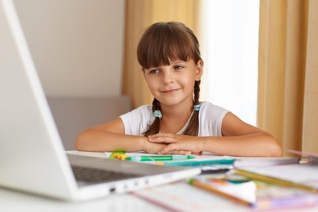 Retrato de colegial com cabelo escuro e rabo de cavalo, sentado à mesa na sala de estar. professora ouvinte online, tendo aula a distância em quarentena, usufruindo de educação à distância.