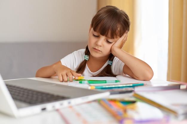 Retrato de colegial entediada de camiseta branca, sentada à mesa, na frente do caderno, com uma expressão facial triste, cansada de fazer o dever de casa, educação a distância.