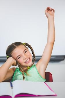 Retrato de colegial, levantando a mão na sala de aula