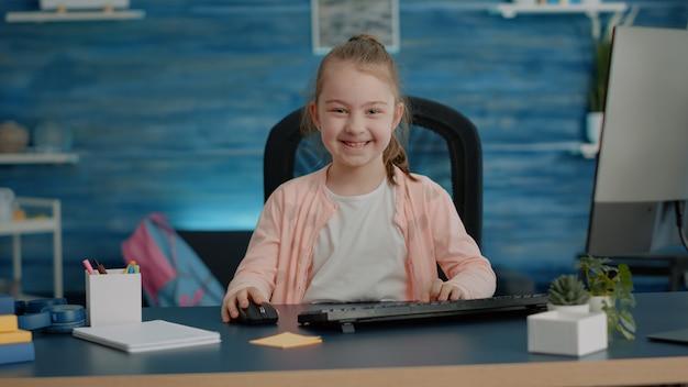 Retrato de colegial na mesa usando computador e teclado