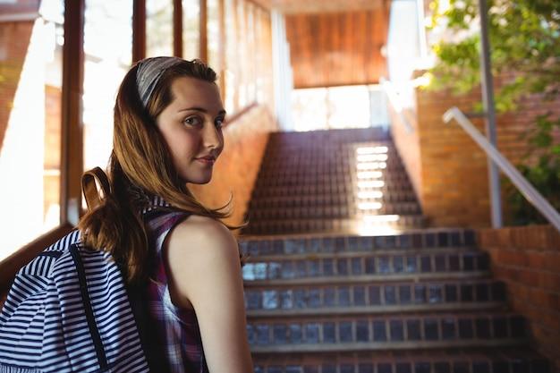 Retrato de colegial para mochila em pé perto da escada