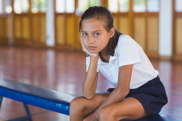 Retrato de colegial sentado na quadra de basquete