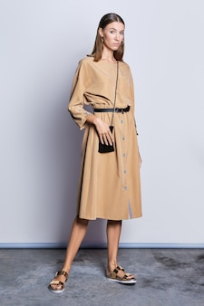 Retrato de comprimento cheio de modelo linda no vestido de cor areia no fundo cinza
