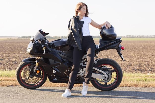 Retrato de comprimento total de atraente mulher bonita olhando de lado, em pé perto de seu veículo, colocando o braço no capacete, vestindo jaqueta de couro, camiseta branca, calça preta e tênis branco.